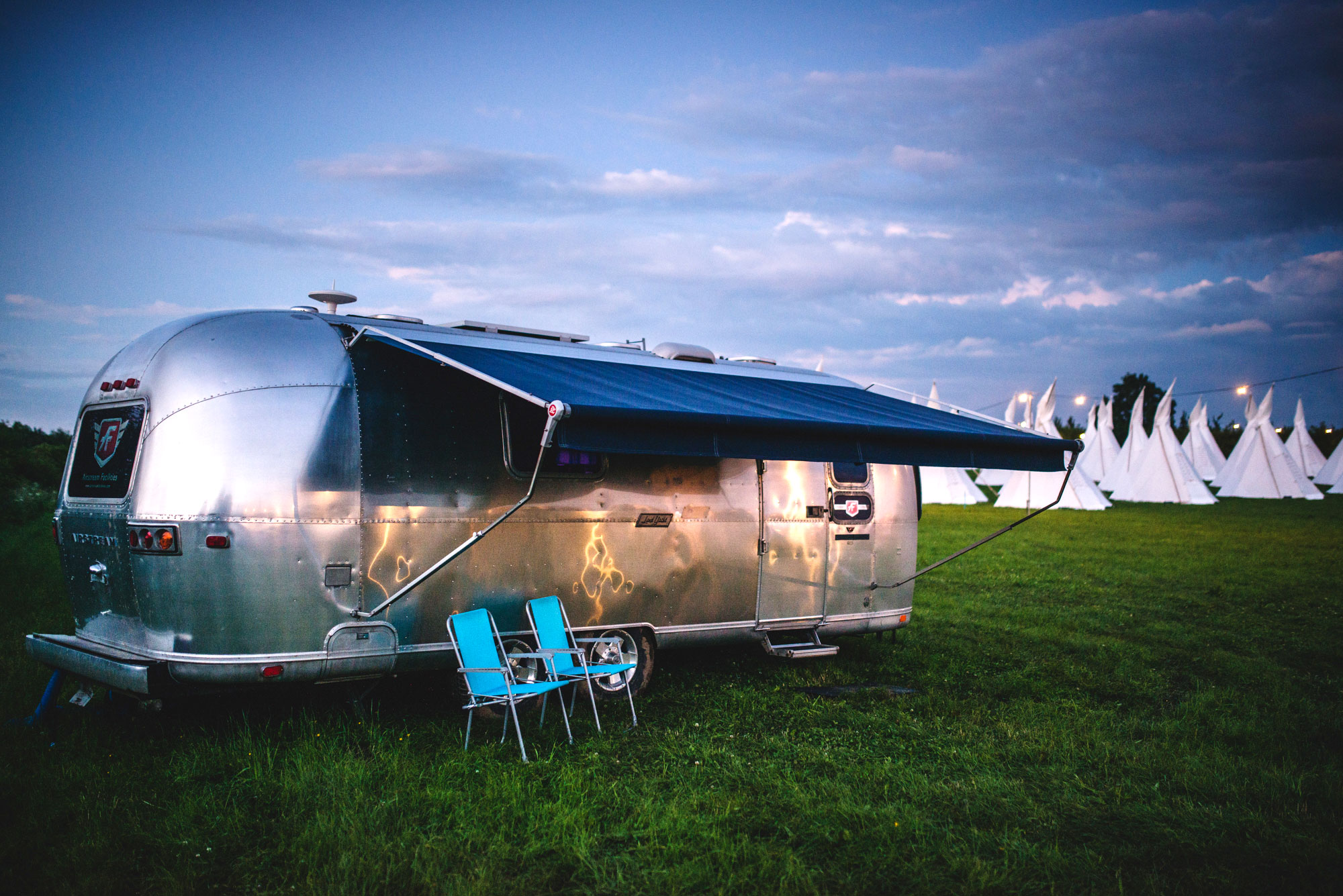 Airstream caravan with awning and chairs at dusk in the Pennard Orchard field