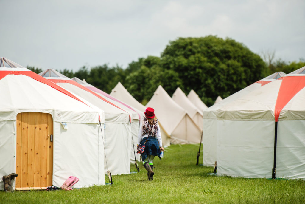 Guest walking to her luxury yurt at Pennard Orchard during Glastonbury Festival