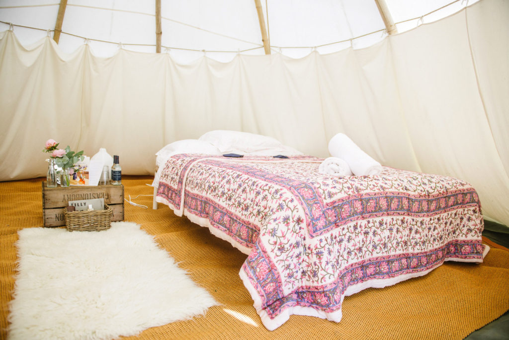 Majestic tipi for two with pink quilt at Pennard Orchard boutique Camping for Glastonbury Festival